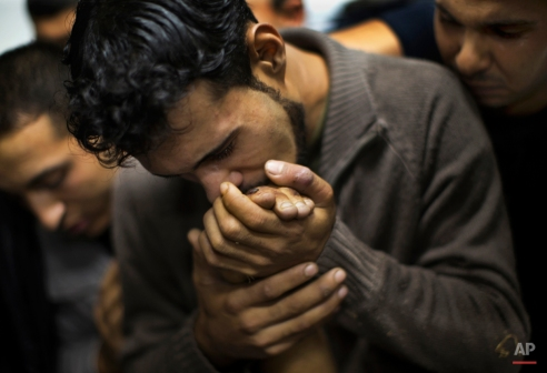 In this Nov. 18, 2012 photo, a Palestinian man kisses the hand of a dead relative in the morgue of Shifa Hospital in Gaza City. This photo was one in a series of images by Associated Press photographer Bernat Armangue that won the first place prize in the World Press Photo 2013 photo contest for the Spot News series category. (AP Photo/Bernat Armangue)