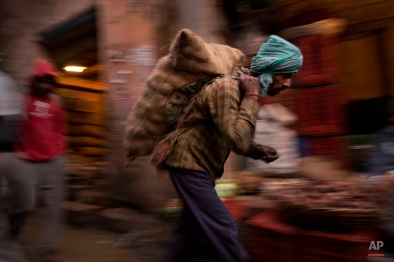 An Indian laborer carries a sack full of vegetables at a wholesale vegetable market in old parts of New Delhi, India, Monday, Dec. 15, 2014. Old Delhi despite of being extremely crowded and dilapidated still serves as the symbolic heart of the city. (AP Photo/Bernat Armangue)