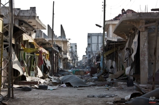 In this Wednesday, Nov. 19, 2014 photo shows destruction in the town market place in Kobani, Syria. In a surprising display of resilience, the Kurdish fighters have held out against the more experienced jihadists more than two months into the Islamic State group militants' offensive on the frontier town, hanging on to their territory against all expectations. (AP Photo/Jake Simkin)