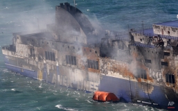 """Smoke billows from the Italian-flagged Norman Atlantic ferry that caught fire in the Adriatic Sea, Tuesday, Dec. 30, 2014. A blaze broke out on the car deck of the Norman Atlantic Sunday, Dec. 28, while the ferry was traveling from the Greek port of Patras to Ancona in Italy causing the death of at least 11 people. Italian and Greek helicopter rescue crews evacuated 427 people among passengers and crew members but Italian officials think the death toll could be much higher because of serious discrepancies in the ship's manifest and confusion over how many people were aboard. """"We cannot say how many people may be missing,"""" Italian Transport Minister Maurizio Lupi said at a news conference. The cause of the fire is under investigation. (AP Photo/Antonio Calanni)"""