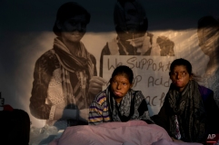 Acid attack victims Rupa, 19, center, and Ritu 18, sit on a hunger strike demanding strict laws to deal with acid attacks, in New Delhi, India, Monday, Dec. 15, 2014. Both are victims of acid attacks by their relatives. (AP Photo /Manish Swarup)