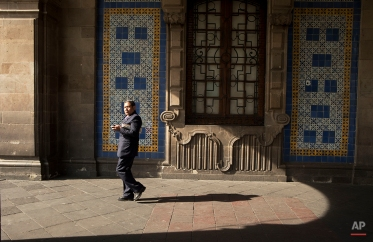 A man walks through a building's colonnade at the start of the work day in the historic center of Mexico City, Monday, May 5, 2014. (AP Photo/Rebecca Blackwell)