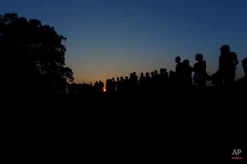 In this photo taken on July 26, 2014, the sun sets as people attend an homage to those killed by their political ideology during and after the Spanish civil war at the site where four mass graves with at least 80 skeletons where found in El Estepar, Spain. (AP Photo/Daniel Ochoa de Olza)