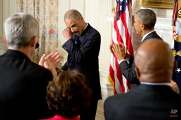 President Barack Obama, right, and the audience applaud as Attorney General Eric Holder wipes his eye, in the State Dining Room of the White House in Washington, Thursday, Sept. 25, 2014, where the president announced that Holder is resigning. Holder, who served as the public face of the Obama administration's legal fight against terrorism and weighed in on issues of racial fairness, is resigning after six years on the job. He is the first black U.S. attorney general. (AP Photo/Carolyn Kaster)