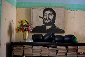 An old photo of Che Guevara hangs on a wall next to several boxing gloves and books in Havana, Cuba, Thursday, Dec. 18, 2014. The United States and Cuba have agreed to establish diplomatic relations and open economic and travel ties, marking the most significant shift in U.S. policy toward the communist island in decades, American officials said Wednesday. (AP Photo/Ramon Espinosa)