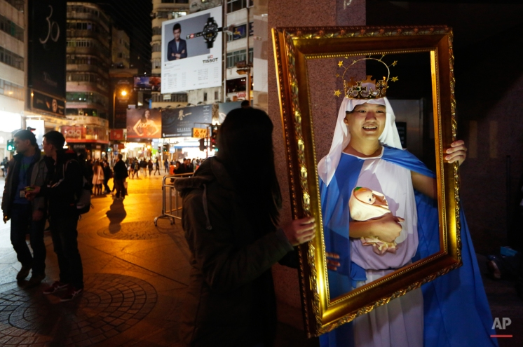 A man dressed as the Virgin Mary with baby Jesus poses for photographs during the early hours of Christmas Day celebrations in the Causeway Bay shopping district in Hong Kong Thursday, Dec. 25, 2014. (AP Photo/Kin Cheung)