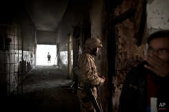 A Pakistani army officer, walks in a corridor riddled with bullet marks, as a man, right, covers his nose form the smell of the blood, inside the Army Public School attacked last Tuesday by Taliban gunmen, in Peshawar, Pakistan, Thursday, Dec. 18, 2014. (AP Photo/Muhammed Muheisen)