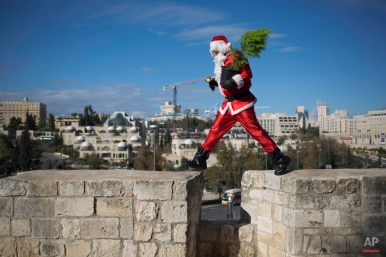A man dressed as Santa Claus walks on the wall of the Old City in Jerusalem Monday, Dec. 22, 2014. (AP Photo/Dusan Vranic)