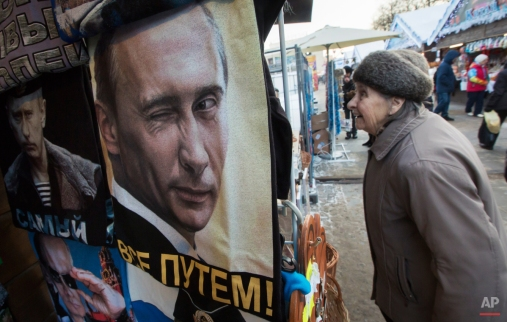A woman chooses purchases next to a kiosk selling T-shirts with a portrait of the Russian President Vladimir Putin at a Christmas market in St.Petersburg, Russia, Wednesday, Dec. 24, 2014. The sign on the T-shirt signs 'Putin is all right '. (AP Photo/Dmitry Lovetsky)