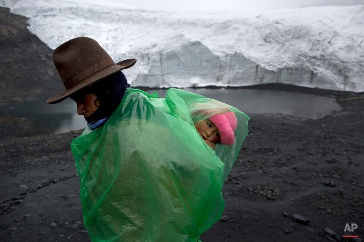 Fausta Ortiz, 38, Pastoruri's glacier guardian, stands guard while carrying her daughter Lisoyun, 2, in Huaraz, Peru, Thursday, Dec. 4, 2014. According to Alejo Cochachin, coordinator of the glaciology unit, the Pastoruri glacier retreated 576 meters between 1980 and 2014. (AP Photo/Rodrigo Abd)