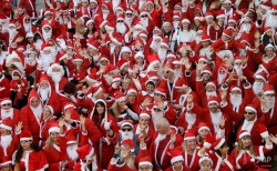 Around 250 people dressed in Santa Claus costumes pose for photographers before a parade in the streets of Vallauris, southeastern France, Saturday, Dec. 20, 2014. (AP Photo/Lionel Cironneau)