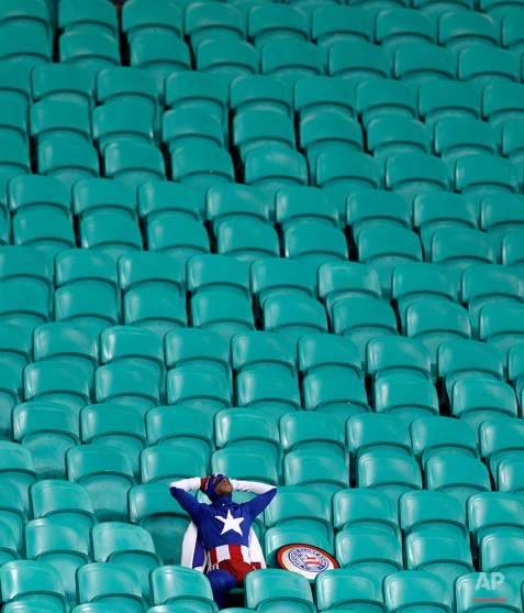 A lone USA supporter dressed as 'Captain America' sits in the stands after Belgium defeated the USA 2-1 in extra time to advance to the quarterfinals during the World Cup round of 16 soccer match between Belgium and the USA at the Arena Fonte Nova in Salvador, Brazil, Tuesday, July 1, 2014. (AP Photo/Natacha Pisarenko)