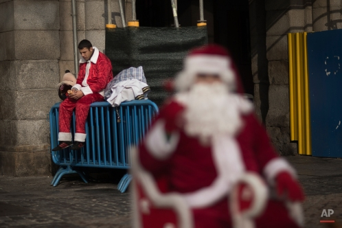 A man who performs for money wearing a Santa Claus outfit eats a sandwich as he takes a break at the Madrid's Christmas market in Madrid, Spain, Saturday, Dec. 13, 2014. (AP Photo/Andres Kudacki)