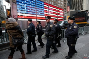 New York City police officers patrol in Times Square, Tuesday, Dec. 30, 2014, in New York. Preparations are under way for New Year's Eve celebrations, which draw millions of spectators from around the world. (AP Photo/Kathy Willens)