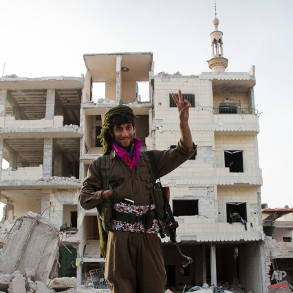 In this Wednesday, Nov. 1, 2014 photo, Kurdish fighter Azzad, who lost his hand in a farming accident, takes a break from the battlefield in Kobani, Syria. (AP Photo/Jake Simkin)
