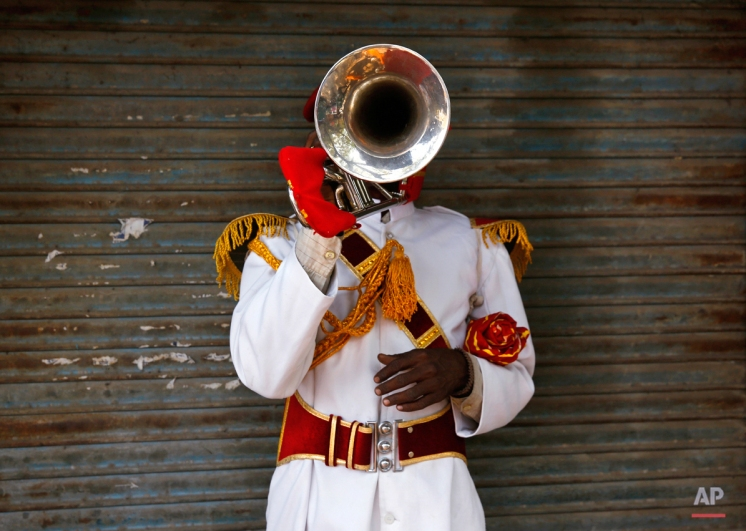 In this Monday, Nov. 3, 2014 photo, Ram Charan, 35, from Bareilly some 256 kilometers (160 miles) from Delhi, a member of Master Band, an Indian brass band specialized in playing weddings, poses for a portrait in New Delhi. (AP Photo/Manish Swarup)