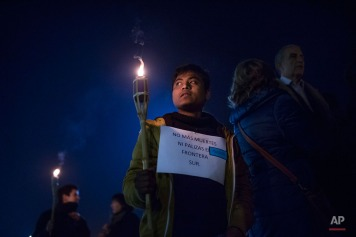"""A protester carries a torch and a banner that reads: """"No More Deaths or Beatings on the South Border"""", during a protest against the Public Security Law and Spanish policies on immigration in front of the Royal Palace in Madrid, Spain, Thursday, Dec. 18, 2014. Spain's lower house of parliament approved last Thursday the Public Security Law that allows for the summary expulsion of migrants entering the country's North African enclaves illegally. The legislation also says organizers of demonstrations outside parliament buildings and key installations that are deemed to be disturbing the peace can be fined. (AP Photo/Andres Kudacki)"""
