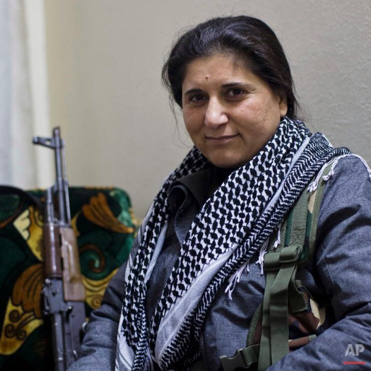 In this Nov. 21, 2014 photo, Asya Abdullah, chairwoman of the Syrian Kurdish Democratic Union Party (PYD), the biggest Kurdish party in western Kurdistan (north and northeastern Syria). poses for a portrait in Kobani, Syria. (AP Photo/Jake Simkin)