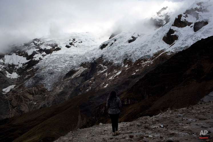 A woman looks to the glacier Contrayerba in the Huascaran National Park in Huaraz, Peru, Wednesday, Dec. 3, 2014. Peru's glaciers have lost more one-fifth of their mass in just three decades, and the 70 percent of Peru's 30 million people who inhabit the country's Pacific coastal desert, depend on glacial runoff for hydropower and to irrigate crops, meaning their electricity and long-term food security could also be in peril. Higher alpine temperatures are killing off plant and animal species in cloud forests and scientists predict Pacific fisheries will suffer. (AP Photo/Rodrigo Abd)