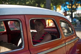 A woman waits in a classic American car that's used as a shared taxi by commuters in Havana, Cuba, early Thursday, Dec. 18, 2014. After a half-century of Cold War acrimony, the United States and Cuba abruptly moved on Wednesday to restore diplomatic relations, a historic shift that could revitalize the flow of money and people across the narrow waters that separate the two nations. (AP Photo/Ramon Espinosa)