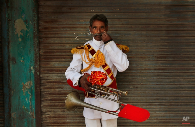 In this Nov. 3, 2014, photo, Shivshankar, 55, from Pali, some 553 kilometers (344 miles) from Delhi, a member of Master Band, an Indian brass band specialized in playing weddings, poses for a portrait in New Delhi. (AP Photo/Manish Swarup)
