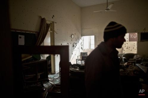 A Pakistani man checks the damage inside the room of headmaster Tahira Kazi, 58, who was killed in Tuesday's Taliban attack on a military-run school in Peshawar, Pakistan, Thursday, Dec. 18, 2014. (AP Photo/Muhammed Muheisen)