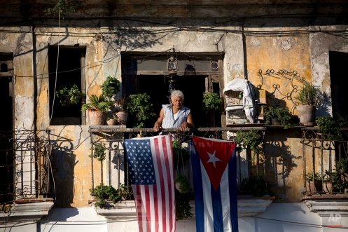 Javier Yanez stands on his balcony where he hung a U.S. and Cuban flag in Old Havana Cuba, Friday, Dec. 19, 2014. After the surprise announcement on Wednesday of the restoration of diplomatic ties between Cuba and the U.S., many Cubans expressed hope that it will mean greater access to jobs and the comforts taken for granted elsewhere, and lift their struggling economy. However others feared a cultural onslaught, or that crime and drugs, both rare in Cuba, will become common along with visitors from the United States. (AP Photo/Ramon Espinosa)
