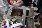 """In this Feb. 5, 2014 photo, Divaldo Aguiar, who plays the part of Pachencho, lies inside a mock coffin as villagers splash rum into Aguiar's mouth during the Burial of Pachencho celebration at a cemetery in Santiago de Las Vegas, Cuba. The bash kicked off with the slow procession to the local cemetery as pallbearers carried the coffin of """"Pachencho,"""" known the other 364 days of the year as Divaldo Aguiar, to an open grave and used ropes to lower it six feet under. (AP Photo/Franklin Reyes)"""