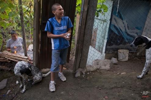 In this Tuesday, Nov. 25, 2014 photo, Roberto Castellanos smiles while he shows golf balls he collected at the Jardines del Country neighborhood in Tegucigalpa, Honduras. (AP Photo/Esteban Felix)