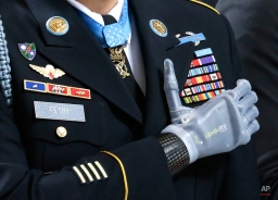 "Medal of Honor recipient Sgt. 1st Class Leroy Petry stands with his prosthetic hand over his heart, wearing his Medal of Honor during the ""Pledge of Allegiance"" at the Capitol in Olympia, Wash. on Wednesday, April 2, 2014, during a ceremony to honor him and other recipients of the Medal of Honor from Washington state. Petry lost his hand in 2008 when an enemy grenade he was throwing away from fellow soldiers detonated while in combat in Afghanistan. (AP Photo/Ted S. Warren)"