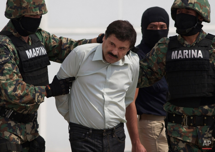 """In this Feb. 22, 2014 photo, Joaquin """"El Chapo"""" Guzman is escorted to a helicopter in handcuffs by Mexican navy marines at a navy hanger in Mexico City, Mexico. Guzman, the head of Mexico's Sinaloa Cartel, was captured alive overnight in the beach resort town of Mazatlan. (AP Photo/Eduardo Verdugo)"""