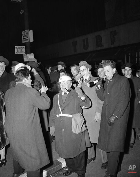 An air raid warden on duty in Times Square in New York City on Jan. 1, 1943, lifts a hand in salute as New Year's celebrants swirl past him. (AP Photo/John Lindsay)