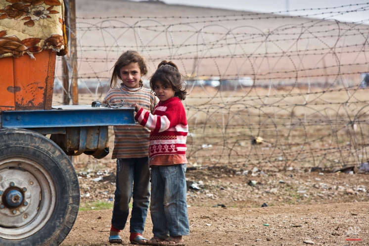 In this Saturday, Nov. 22, 2014 photo, children by the fence line with Turkey in Kobani, Syria. Here, Kurdish fighters backed by small numbers of Iraqi peshmerga forces and Syrian rebels, are locked in what they see as an existential battle against the Islamic State group, who swept into their town in mid-September as part of a summer blitz after the Islamic State group overran large parts of Syria and neighboring Iraq. But the battle comes with an onerous price for the town's residents. While most managed to flee across the nearby border with Turkey, some 2,000 Kurdish civilians have opted to stay with the hope that fighting will soon subside _ a shocking contrast from the population of 50,000 that once filled these streets. (AP Photo/Jake Simkin)