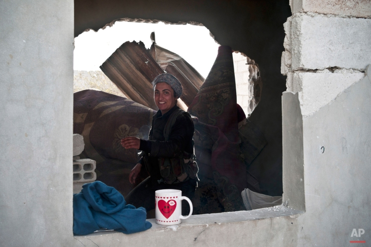 In this Nov. 1, 2014 photo, a female Kurdish fighter is seen in Kobani, Syria. On the front lines of the battle for Kobani, Kurdish female fighters have been playing a major role in helping defend the Syrian town from an onslaught by the Islamic State extremist group. (AP Photo/Jake Simkin)