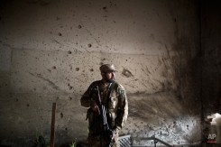 A Pakistani army officer, stands in front of a wall riddled with bullet marks, inside the Army Public School attacked last Tuesday by Taliban gunmen, in Peshawar, Pakistan, Thursday, Dec. 18, 2014. (AP Photo/Muhammed Muheisen)