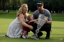 Zoe Mahan, center, pushes the trophy as her mother Kandi Mahan, left, grabs her while they pose with Hunter Mahan, husband, father and winner of The Barclays golf tournament Sunday, Aug. 24, 2014, in Paramus, N.J. (AP Photo/Mel Evans)