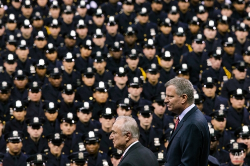 New York City Mayor Bill de Blasio, right, and NYPD police commissioner Bill Bratton, center, stand on stage during a New York Police Academy graduation ceremony, Monday, Dec. 29, 2014, at Madison Square Garden in New York. Nearly 1000 officers were sworn in as tensions between city hall and the NYPD continued following the Dec. 20 shooting deaths of officers Rafael Ramos and Wenjian Liu. (AP Photo/John Minchillo)