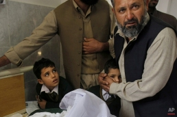A Pakistani man comforts a student standing at the bedside of a boy who was injured in a Taliban attack on a school, at a local hospital in Peshawar, Pakistan, Tuesday, Dec. 16, 2014. Taliban gunmen stormed a military-run school in the northwestern Pakistani city of Peshawar on Tuesday, killing more than 100, officials said, in the worst attack to hit the country in over a year. (AP Photo/Mohammad Sajjad)