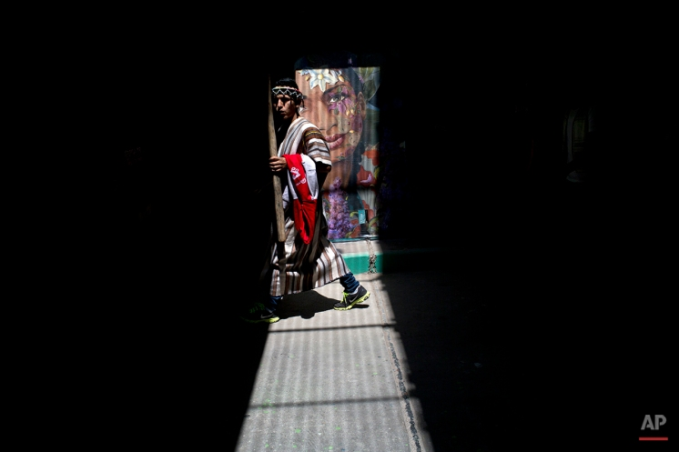 An Indian man walks though a tunnel decorated with several murals during the Climate Change Conference in Lima, Peru, Monday, Dec. 1, 2014. Delegates from more than 190 countries will meet in Lima for the next two weeks to work on drafts for a global climate deal that is supposed to be adopted next year in Paris. (AP Photo/Rodrigo Abd)