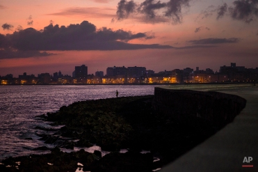 A fisherman casts his line along the Malecon at sunrise in Havana, Cuba, Wednesday, Oct. 8, 2014. (AP Photo/Ramon Espinosa)