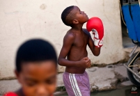 Youths sharing a pair of boxing gloves practice punches as they walk home after working out at a gym in Old Havana, Cuba, Saturday, Oct. 20, 2012. (AP Photo/Ramon Espinosa)