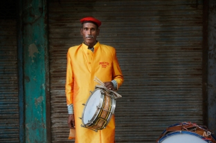In this Monday, Nov. 3, 2014, photo, Ramcharan, 60, from Jhasi some 443 kilometres (276 miles) from Delhi, a members of Master Band, an Indian brass band specialized in playing weddings, poses for a portrait in New Delhi. (AP Photo/Manish Swarup)