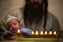 Ultra-Orthodox Jewish Yoel Krois holds his son while his family gather around candles at their home, during the Jewish holiday of Hanukkah in Jerusalem's Mea Shearim neighborhood Sunday, Dec. 21, 2014. (AP Photo/Oded Balilty)