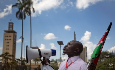 A protester against the new security law, who managed to get past heavy police cordons preventing demonstrations, shouts into a megaphone while holding the Kenyan flag outside the Parliament building in Nairobi, Kenya Thursday, Dec. 18, 2014. Kenyan legislators Thursday exchanged blows on changes to security laws which the government says will help fight terrorism but which critics say are meant to silence dissent by curtailing civil liberties, with opposition legislators throwing the papers on the floor and government supporters hitting and tearing the clothes of an opposition senator. (AP Photo/Ben Curtis)