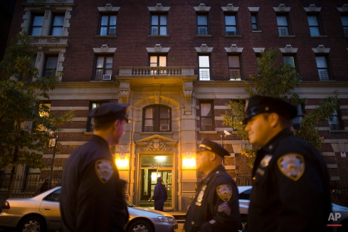 Police officers stand outside the home of Craig Spencer, a Doctors Without Borders physician who recently returned to the city after treating Ebola patients in West Africa, Thursday, Oct. 23, 2014, in New York. Spencer tested positive for the virus. (AP Photo/John Minchillo)