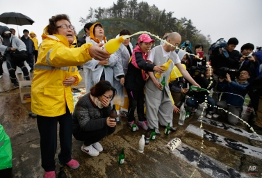 A Buddhist monk and relatives of passengers aboard a sunken ferry spray alcohols during a Buddhist ceremony to pray for speedy rescue and their safety at a port in Jindo, south of Seoul, South Korea, Friday, April 18, 2014. The ferry flipped onto its side and filled with water off the southern coast of South Korea. (AP Photo/Lee Jin-man)