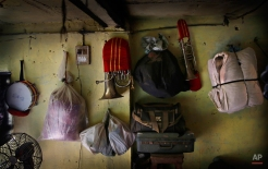 In this Nov. 7, 2014, photo, musical instruments along with personal belongings of members of Master Band are hung on the wall of their barrack, in New Delhi, India. (AP Photo/Manish Swarup)