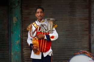 In this Nov. 3, 2014, photo, Mohammad Abid, 55, from Badaun some 263 kilometres (163 miles) from Delhi, a member of Master Band, an Indian brass band specialized in playing weddings, poses for a portrait in New Delhi. Dressed in faded military-style uniforms or long silken tunics and turbans, brass bands playing the latest Bollywood tunes have long been a must-have at any Indian wedding. (AP Photo/Manish Swarup)