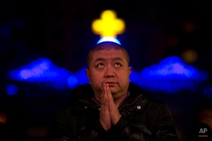 A Chinese man prays during a mass on the eve of Christmas at the South Cathedral official Catholic church in Beijing, China, Wednesday, Dec. 24, 2014. Estimates for the number of Christians in China range from the conservative official figure of 23 million to as many as 100 million by independent scholars, raising the possibility that Christians may rival in size the 85 million members of the ruling Communist Party. (AP Photo/Ng Han Guan)