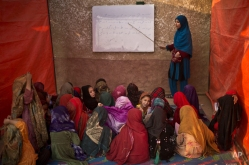 Afghan refugee girls sit on the ground attend a class to learn how to read and write the alphabet at a makeshift school in the outskirts of Islamabad, Pakistan, Monday, Dec. 29, 2014. (AP Photo/Muhammed Muheisen)
